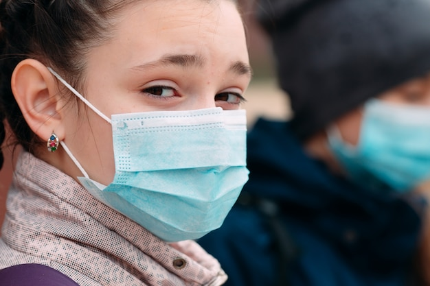 Kinder im schulpflichtigen alter in medizinischen masken. porträt von schulkindern.