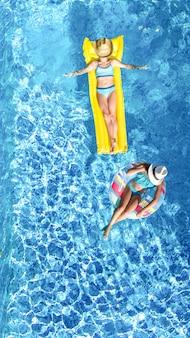 Kinder im schwimmbad luftdrohne blick von oben, glückliche kinder schwimmen auf aufblasbaren ringkrapfen und matratze, aktive mädchen haben spaß im wasser im familienurlaub im ferienort