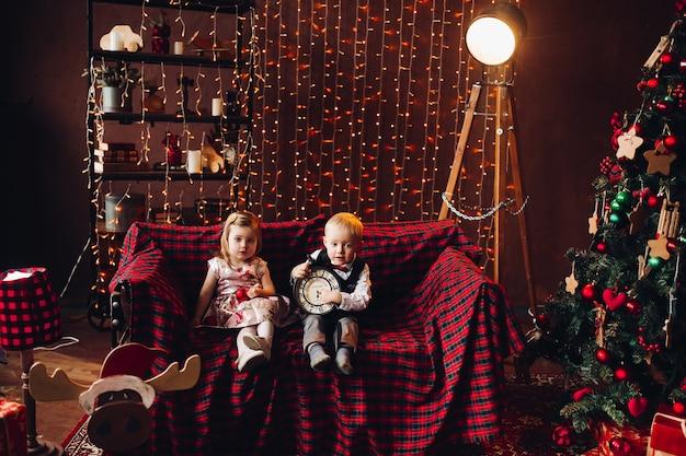 Kinder in dekorierten studio und spielen mit weihnachtsgeschenken