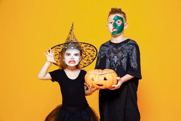 Kinder in den halloween-kostümen, die einen kürbis halten