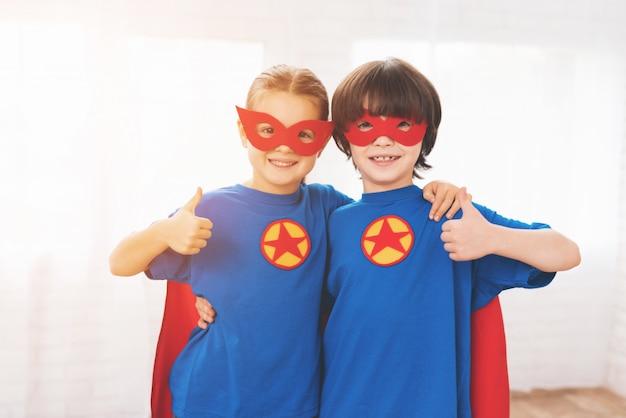 Kinder in den roten und blauen anzügen der superhelden.