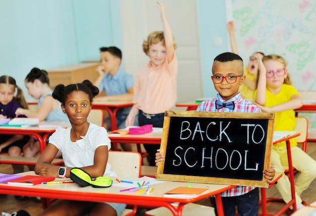 Kinder in der klasse mit schulanfangsschild
