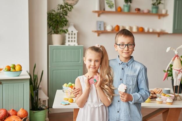 Kinder in der küche an ostertag, junge und mädchen mit ostern-lebkuchen und eiern
