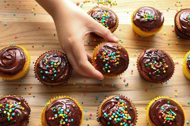 Kinder in der küche! nahaufnahmehand eines kindes, das einen schokoladenkleinen kuchen auf dem brett des kleinen kuchens wählt