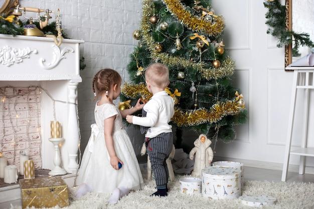 Kinder in der nähe des weihnachtsbaumes, ein junge und ein mädchen verkleiden den weihnachtsbaum