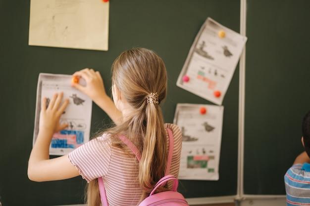 Kinder in der schule stehen an der tafel. grundschule. bildung