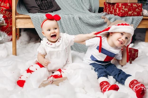 Kinder in der weihnachtskleidung, die im schnee spielt