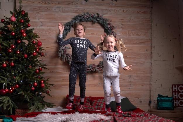 Kinder in derselben familie sehen am weihnachtsabend unter einem geschmückten weihnachtsbaum zu weichen, warmen pyjamas aus. glückliches kind, das auf das bett springt. neujahrsfeiertage.