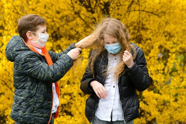Kinder in einem stadtpark in einer medizinischen maske während der quarantänezeit des coronavirus