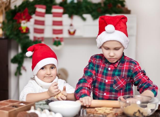 Kinder in einer weihnachtsmannmütze, die weihnachtsplätzchen backt