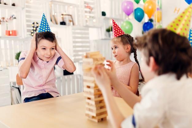 Kinder in farbigen kappen, die hölzernes spiel spielen