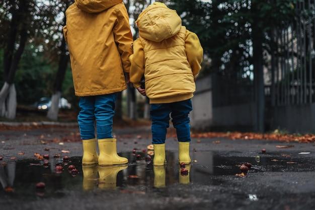 Kinder in gelben gummistiefeln und herbstjacken springen in eine pfütze. herbststimmung.