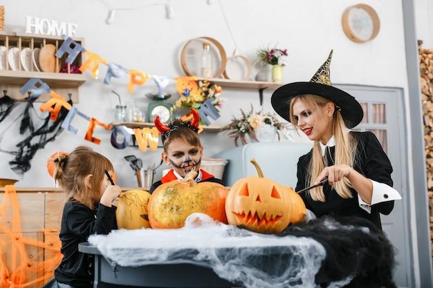 Kinder in gruseligen kostümen malen orangefarbene kürbisse. halloween-konzept. hochwertiges foto