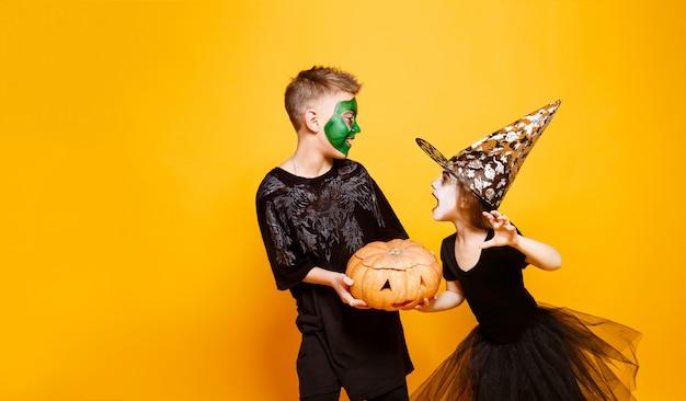 Kinder in halloween-kostümen, die mit kürbis spielen