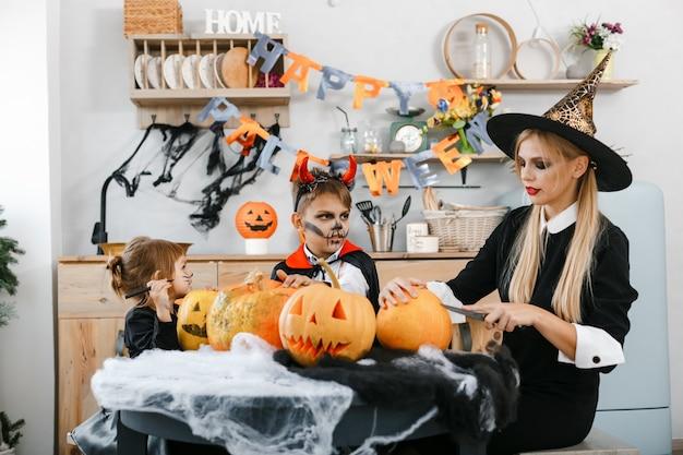 Kinder in halloween-kostümen schnitzen gruselige augen und münder auf kürbisse. hochwertiges foto