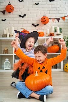 Kinder in halloween-kostümen sitzen in einem dekorierten raum
