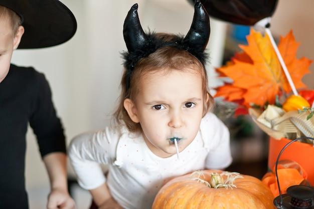 Kinder in hexen- und teufelskostümen für halloween