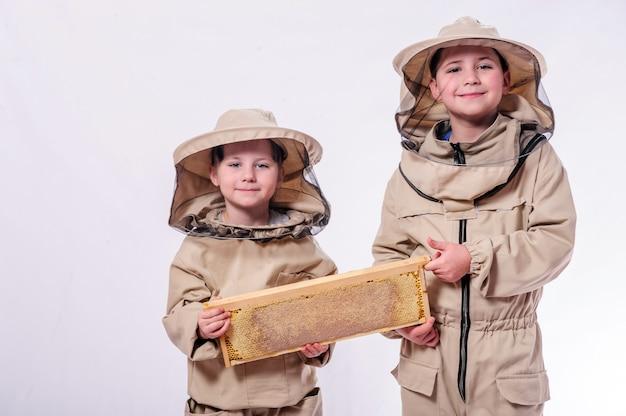 Kinder in imkeranzügen posieren im weißen studiohintergrund.