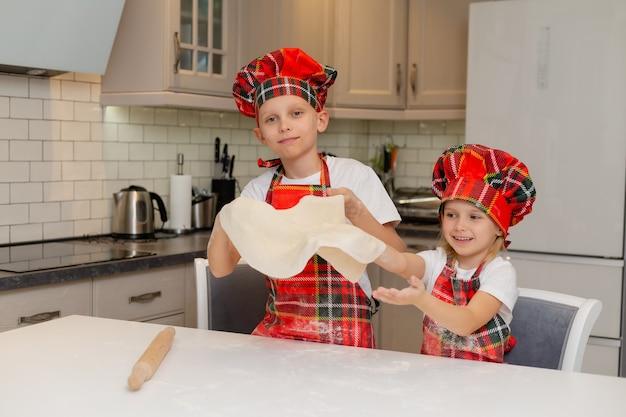 Kinder in kochkostümen rollen den teig mit einem nudelholz für weihnachtsplätzchen aus