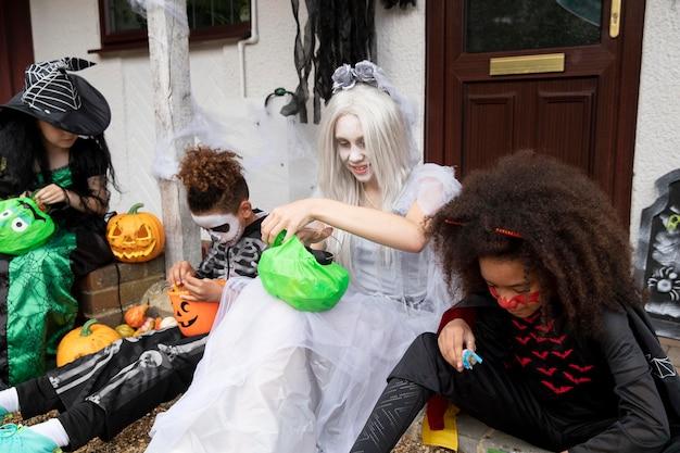 Kinder in kostümen essen ihre süßigkeiten
