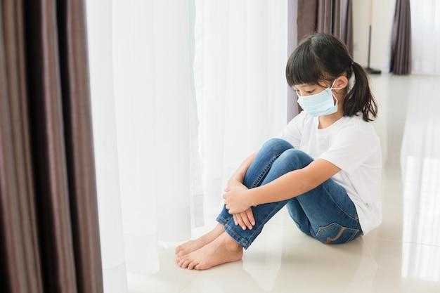 Kinder in medizinischer maske bleiben zur selbstquarantäne zu hause isoliert