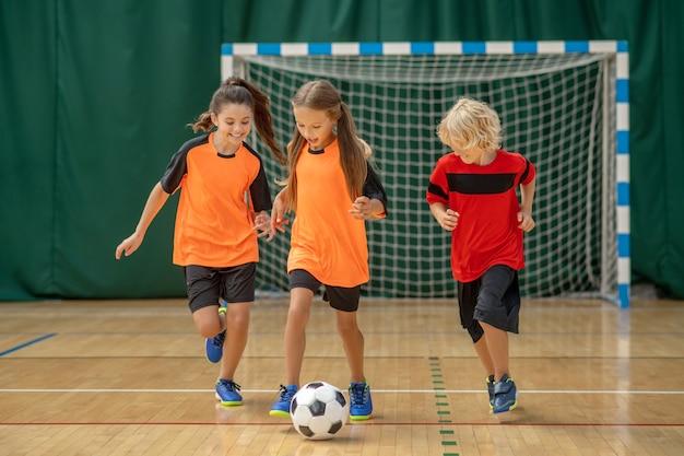 Kinder in sportbekleidung, die dem ball nachlaufen