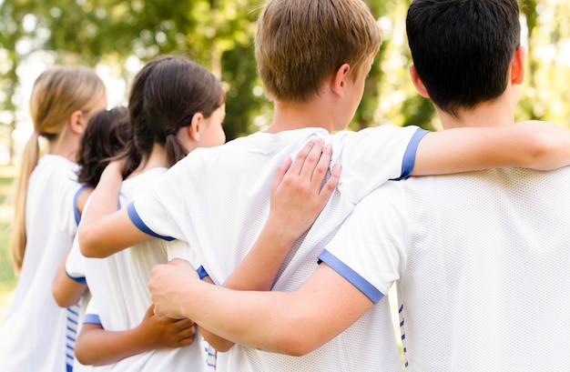 Kinder in sportbekleidung halten sich gegenseitig fest