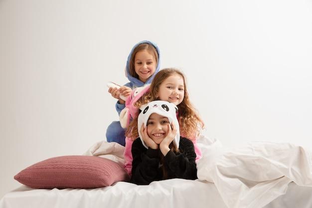 Kinder in weichen, warmen pyjamas, die zu hause hell spielen. kleine mädchen, die spaß haben, feiern, lachen, zusammen spielen, stilvoll und glücklich aussehen. konzept der kindheit, freizeitbeschäftigung, glück.