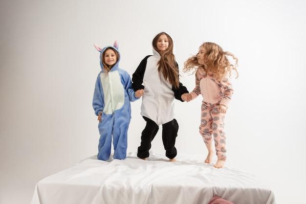 Kinder in weichen, warmen pyjamas, die zu hause in partyfarben hell spielen