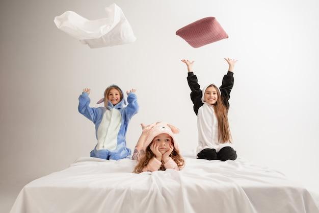 Kinder in weichen, warmen pyjamas spielen zu hause und kämpfen mit kissen. kleine mädchen, die spaß haben, feiern, zusammen lachen, stilvoll und glücklich aussehen. konzept der kindheit, freizeitbeschäftigung, glück.