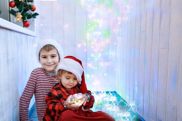 Kinder in weihnachtskostümen mit einem weihnachtsbaumspielzeug. konzept des neuen jahres, maskerade, feiertage, dekorationen