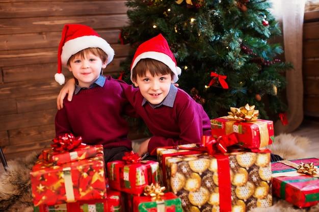 Kinder in weihnachtsmütze mit geschenken in einem haus nahe dem weihnachtsbaum
