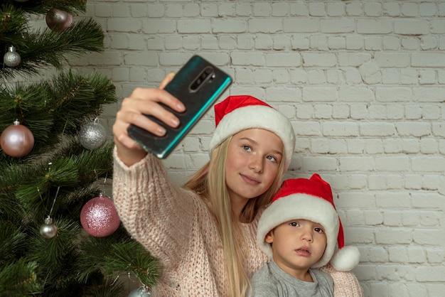 Kinder in weihnachtsmützen machen selfie in der nähe von weihnachtsbaum zu hause, süße geschwister in weihnachtsmützen