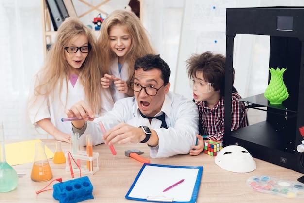 Kinder in weißen kitteln experimentieren während des unterrichts chemisch