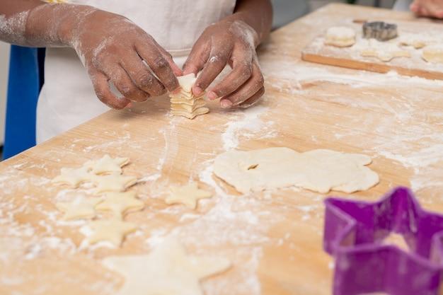 Kinder in weißen schürzen schneiden figuren in ausgerolltem teig und backen leckere kekse für den urlaub