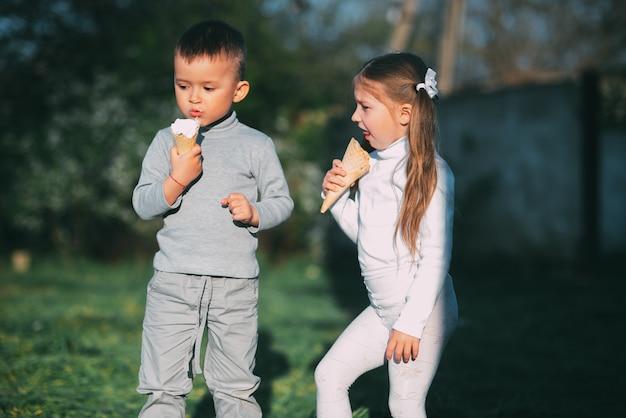 Kinder junge und mädchen essen eis im freien auf gras und bäume hintergrund sehr süß