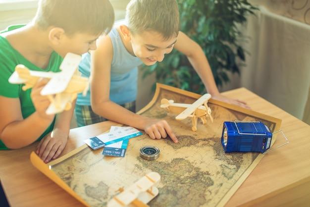 Kinder jungen mit dem flugzeug in der hand, erkunden sie die karte unten, um zu neuen abenteuern zu reisen.