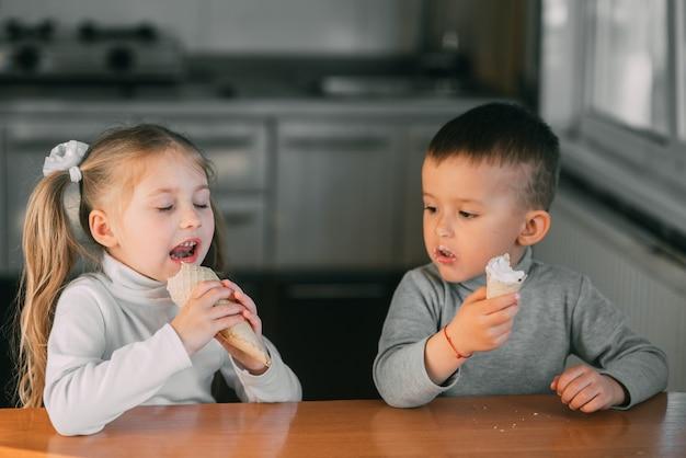 Kinder jungen und mädchen essen eistüte in der küche ist eine menge spaß sehr süß