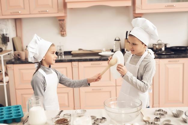 Kinder jungen und mädchen halten ausstechformen in der küche.