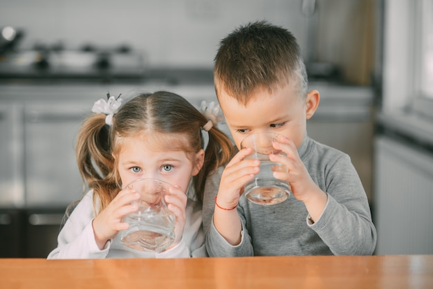 Kinder jungen und mädchen in der küche trinken wasser aus gläsern sehr süß
