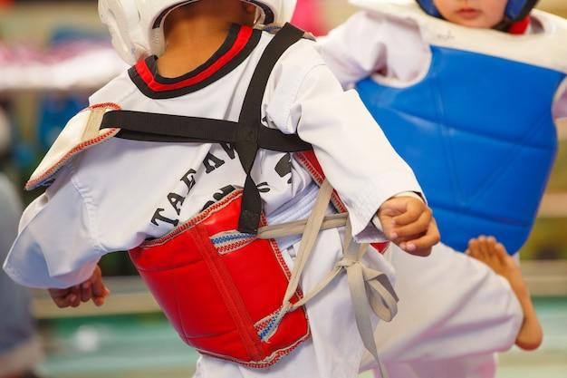 Kinder kämpfen auf der bühne während des taekwondo-turniers