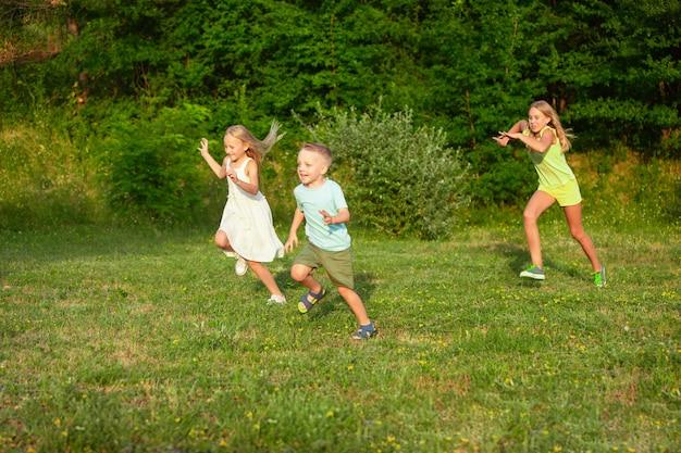 Kinder, kinder, die im sommersonnenlicht auf der wiese laufen. schauen sie glücklich, fröhlich mit aufrichtigen, hellen emotionen aus. nette kaukasische jungen und mädchen. konzept von kindheit, glück, bewegung, familie und sommer.