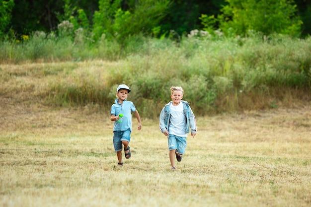 Kinder, kinder, die im sommersonnenlicht auf der wiese laufen. schauen sie glücklich, fröhlich mit aufrichtigen, hellen emotionen aus. nette kaukasische jungen und mädchen.