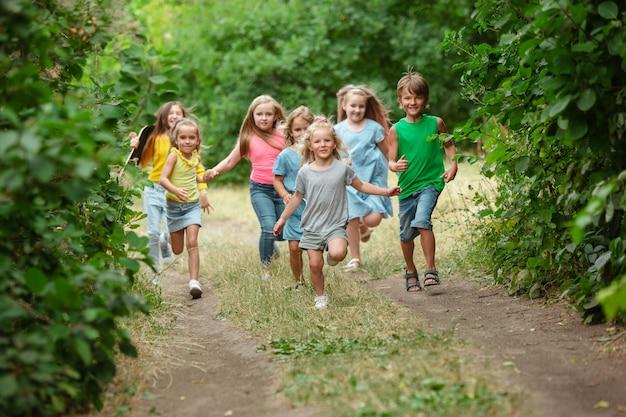 Kinder, kinder laufen auf grüner wiese