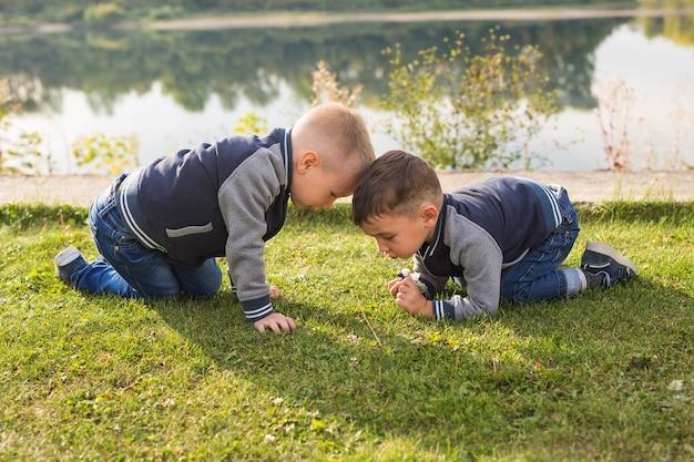 Kinder, kindheit, menschenkonzept - kinderjungen, die an einem strand in der nähe des flusses spielen.