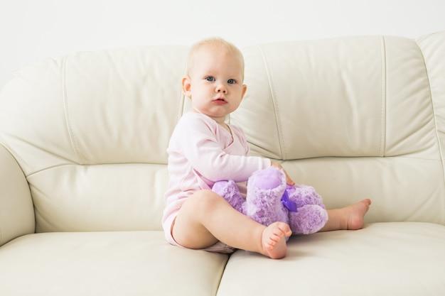 Kinder-, kindheits- und kinderkonzept - schönes lächelndes babysitzen