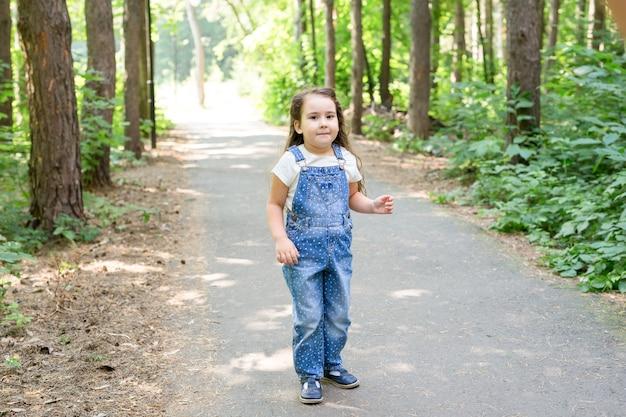 Kinder-, kindheits- und naturkonzept - porträt des schönen kleinen mädchens, das im park spielt.