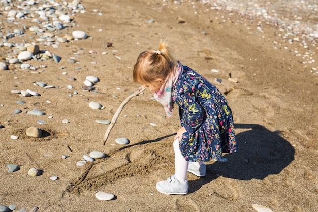 Kinder-, kindheits- und personenkonzept - baby spielen mit stock nahe meeresstrand.