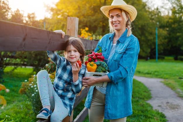 Kinder kleines mädchen halten mutter einen korb mit frischem bio-gemüse Premium Fotos