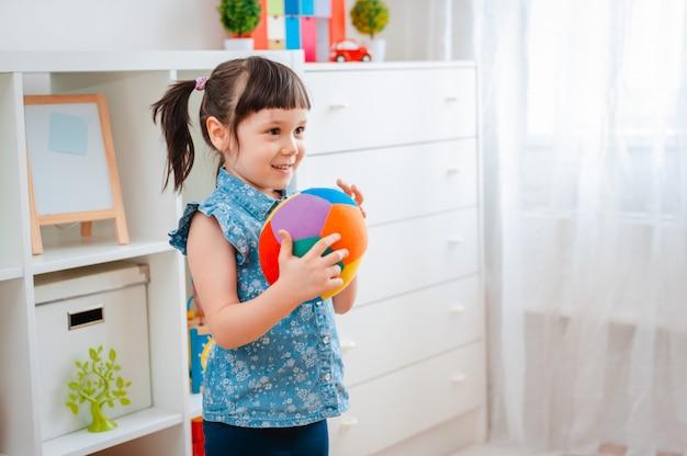 Kinder kleines mädchen spielen in einem kinderspielzimmer und werfen ball. konzept der interaktion eltern und kind